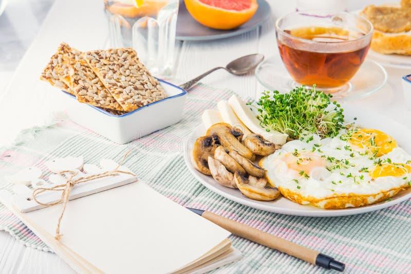 Notatnik z emty pustymi miejscami i zdrowy śniadanie talerz z rozdrapanymi jajkami, serem, piec na grillu pieczarkami i kiełkowym zdjęcia royalty free