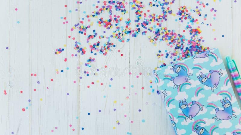 Notatnik z lamy tęczą z kolorowym gel piórem na białym drewnianym tle z confetti i jednorożec Pomysł Girly obrazy royalty free