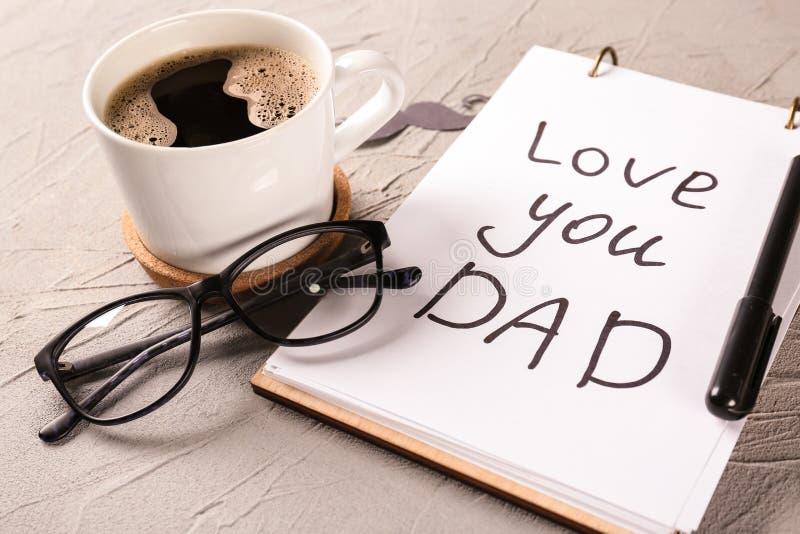Notatnik z miłością TY taty inskrypcja, filiżanka kawy i szkła na popielatym textured tle, Szcz??liwy ojca dnia ?wi?towanie zdjęcie royalty free