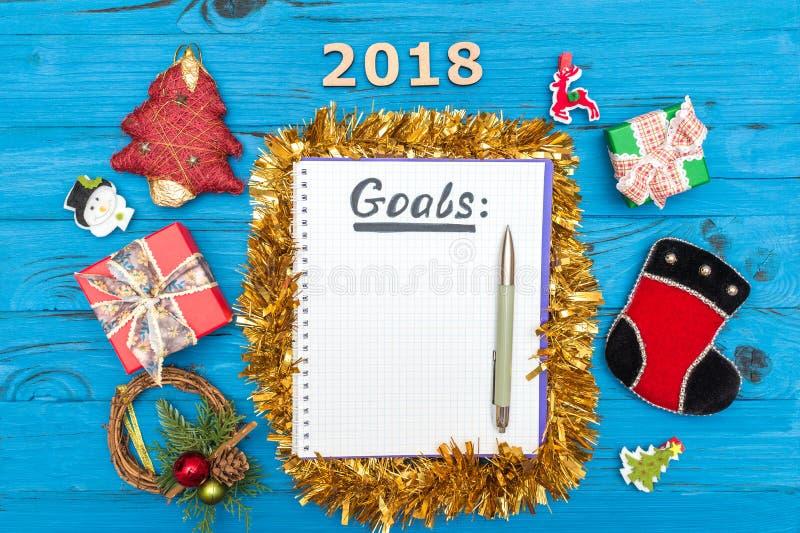 Notatnik z nowy rok celami dla 2018 z piórem, liczby 2018, prezentów pudełka i nowy rok ornamenty na błękicie drewnianym, obraz stock