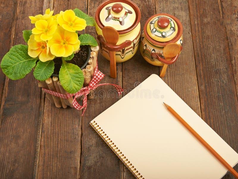 Notatnik z ołówkiem na drewnianym stole z żółtymi pierwiosnkami a obrazy stock
