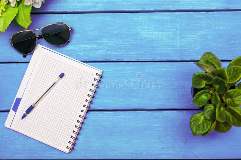 Notatnik z piórem, kwiaty, szkła na błękitnym drewnianym tle fotografia stock