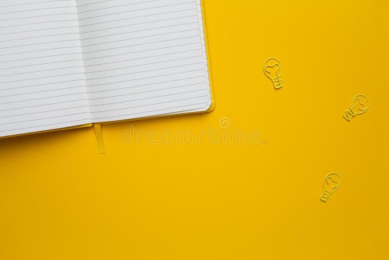 Notatnik z pustymi stronami i paperclip żarówki pomysłem na żółtym tle zdjęcie royalty free