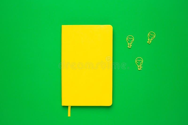Notatnik z pustymi stronami i paperclip żarówki pomysłem na zielonym tle Lata colour flatlay zdjęcie royalty free