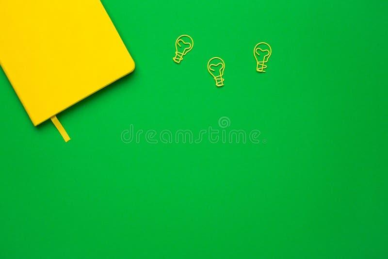 Notatnik z pustymi stronami i paperclip ?ar?wki pomys?em na zielonym tle Lata colour flatlay obraz stock