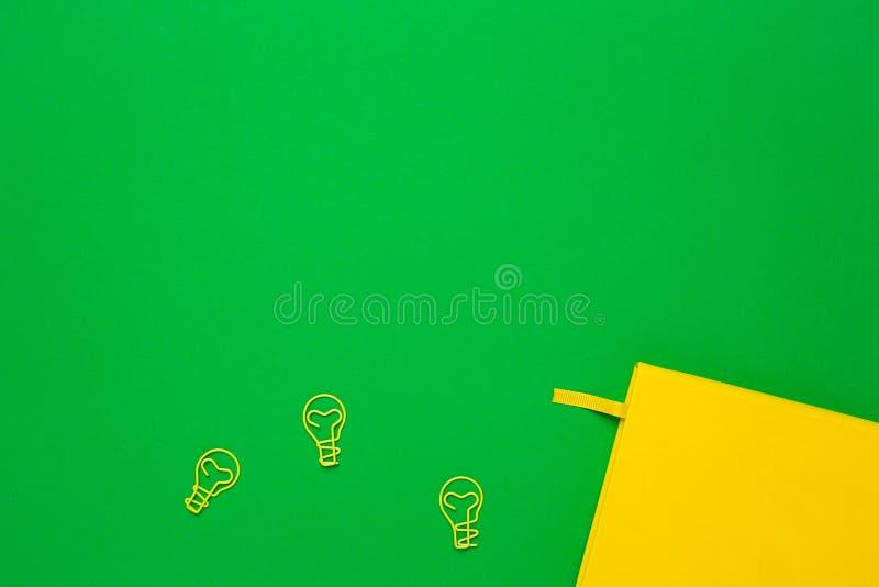 Notatnik z pustymi stronami i paperclip ?ar?wki pomys?em na zielonym tle Lata colour flatlay obraz royalty free
