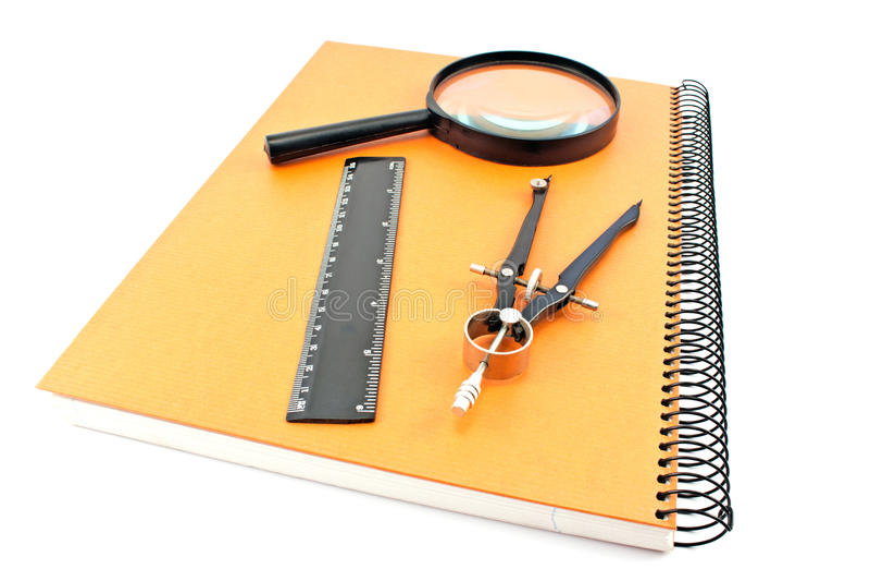 Notatnik z rysunkowym kompasem, władcą i magnifier, zdjęcia stock