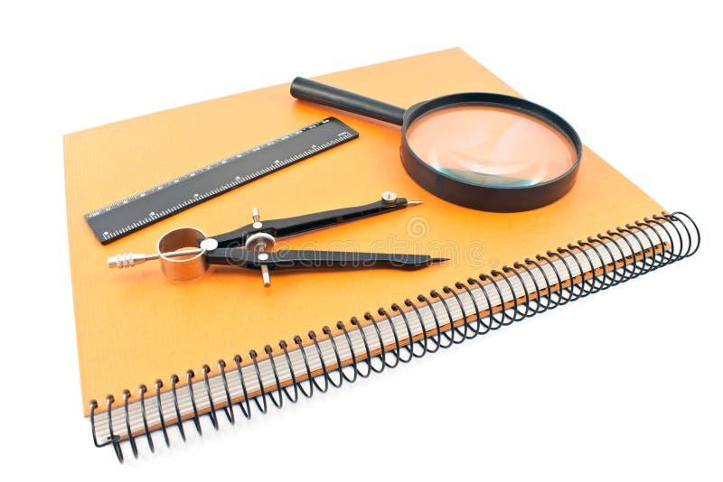 Notatnik z rysunkowym kompasem, władcą i magnifier, zdjęcie royalty free