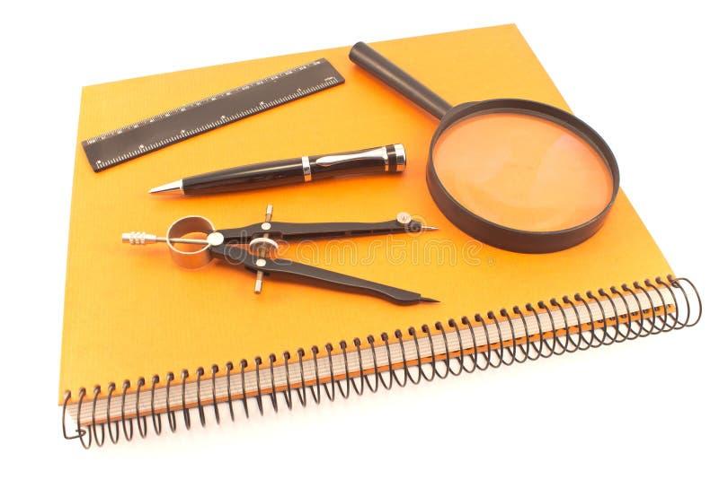 Notatnik z rysunkowym kompasem, władcą i magnifier odizolowywającymi na w, obraz stock
