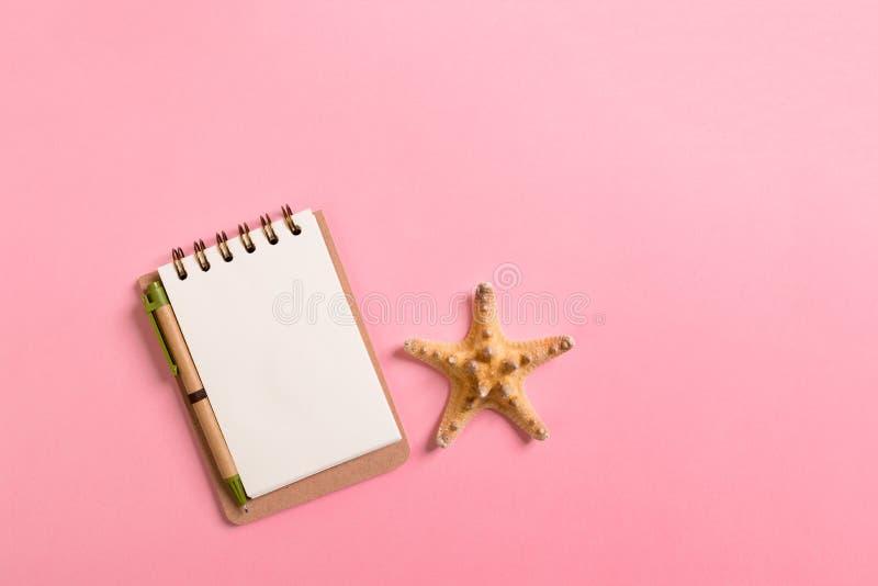 Notatnik z sseashells na różowym tło odgórnego widoku mieszkaniu nieatutowym Planistyczny wakacji letnich, turystyki i wakacje po fotografia stock