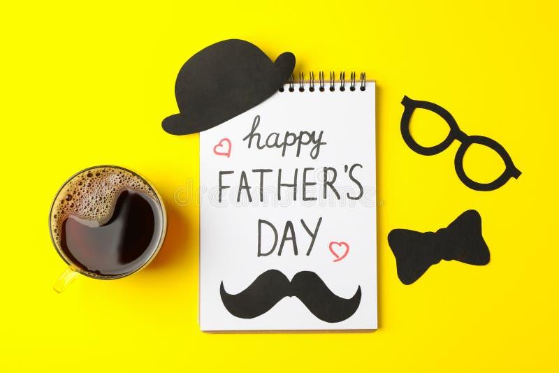 Notatnik z wpisowym szczęśliwym ojca dniem, filiżanka kawy, dekoracyjnym łęku krawatem, szkłami, wąsy i kapeluszem, fotografia stock