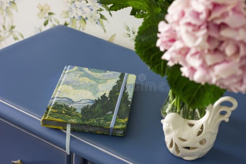 Notatnika dzienniczka książka na błękita stole z bukietem różowe hortensje zdjęcie royalty free