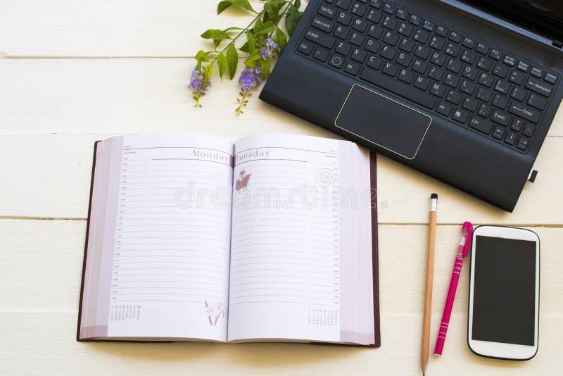 Notatnika obrachunkowy planista, komputer i telefon komórkowy dla biznesowej pracy, fotografia stock