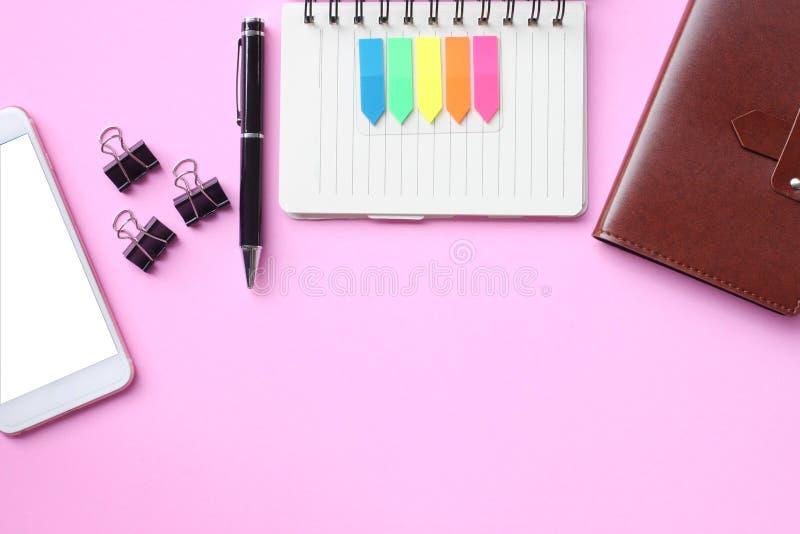 Notatnika smartphone i pióro i umieszczamy na różowej podłodze obrazy royalty free