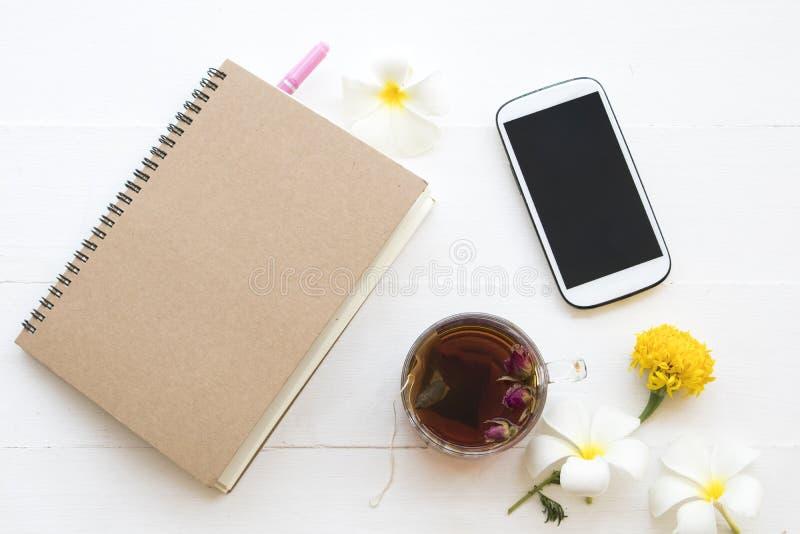 Notatnika, telefonu komórkowego i Ziołowych zdrowych napojów koktajlu gorąca różana herbaciana woda, zdjęcie royalty free