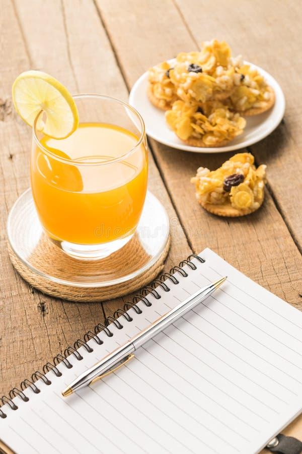 Notatniki z przekąskami i sokiem pomarańczowym na drewnianym stołowym backgro fotografia stock