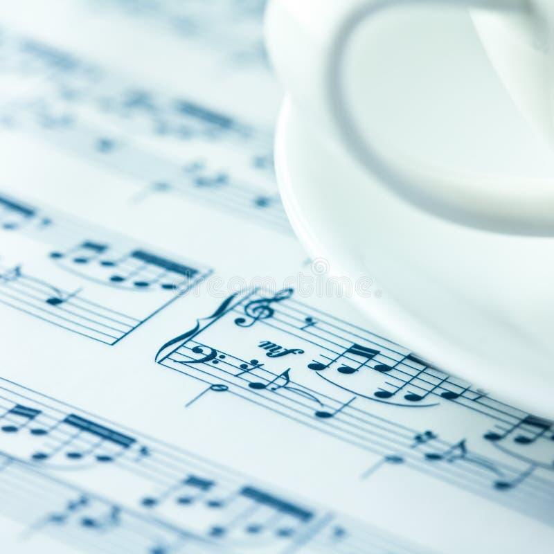 Notazione musicale e una tazza di caffè bianco fotografia stock