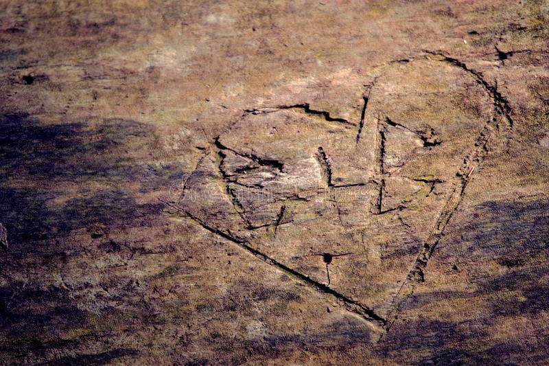Notched Wood. Heart declaring love is etched into a log stock photos