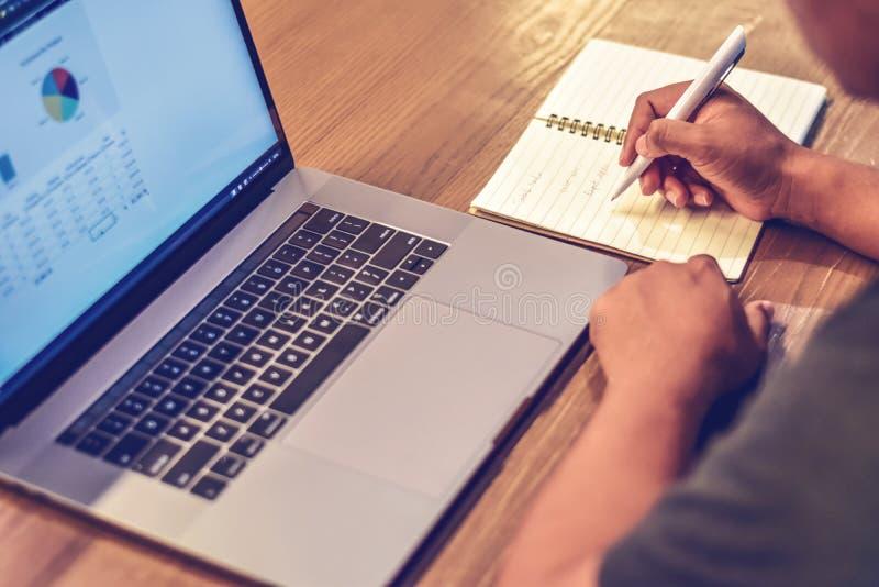 Note adulte d'écriture d'homme sur un carnet près d'ordinateur portable sur un bureau dans le bureau image stock