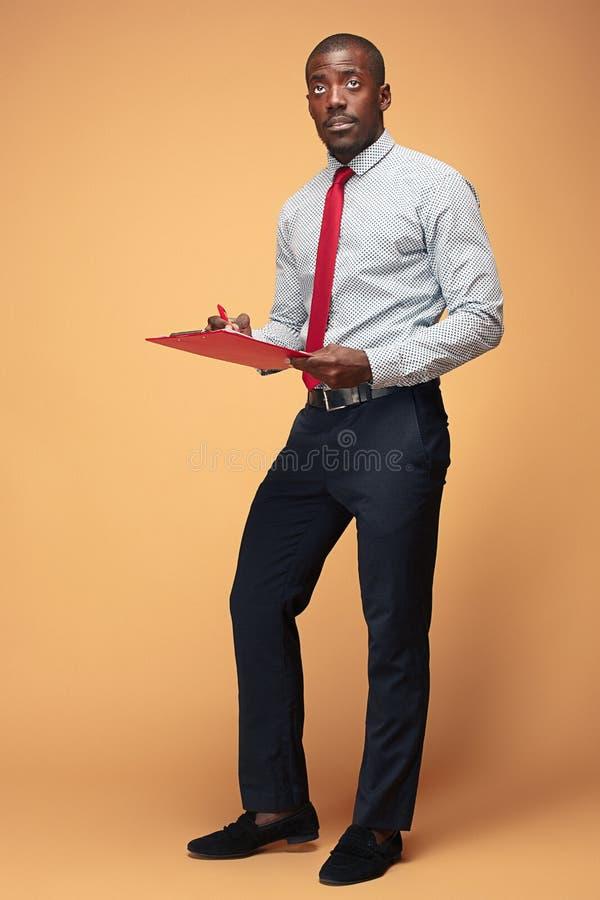 Note afroamericane diritte attraenti di scrittura dell'uomo d'affari fotografia stock libera da diritti