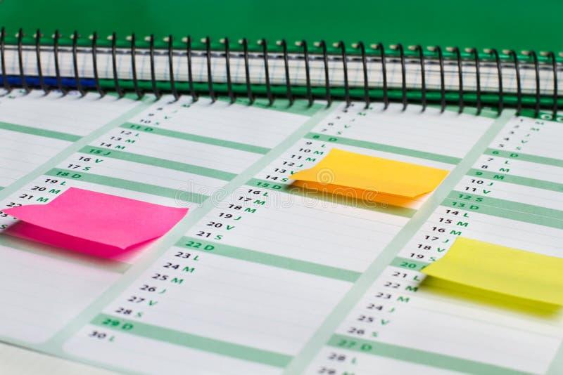 Note appiccicose colorate e un ordine del giorno del lavoro fotografia stock libera da diritti