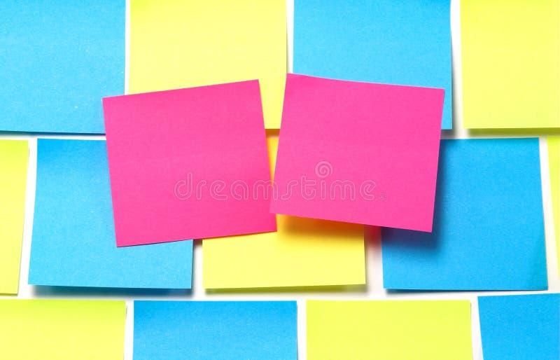 Note appiccicose rosa sul blu e sul giallo immagine stock libera da diritti
