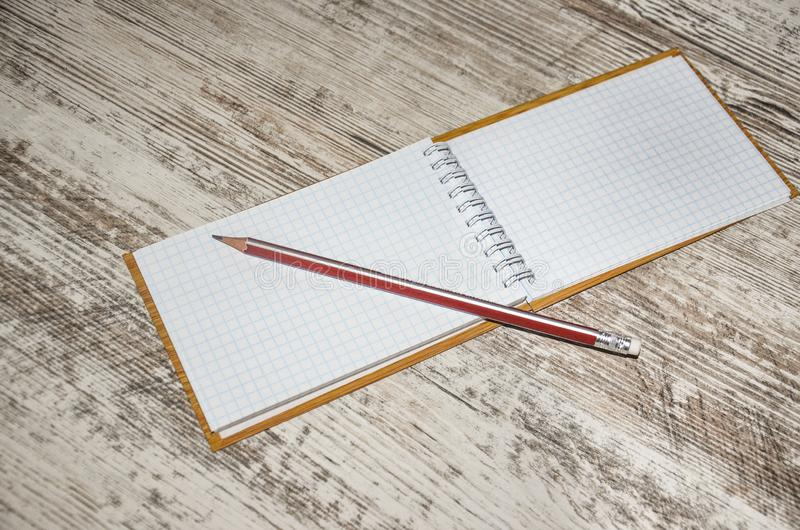 Note book. Blank spiral notebook with pencil laying on wooden desk stock images