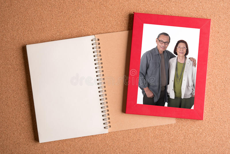 Note book and frame with picture of senior couples on wooden tab. Note book and frame with picture of senior couples on brown wooden table royalty free stock photography