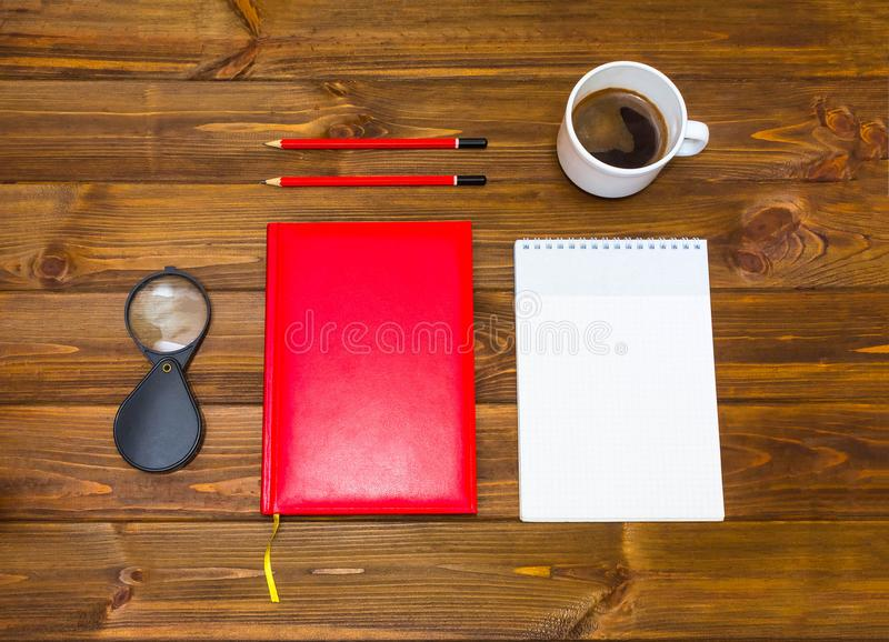Note book and pencil with cup coffee on wooden table stock photos