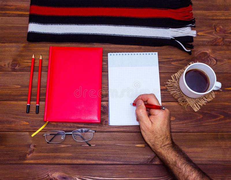 Note book and pencil with cup coffee on wooden table stock photography