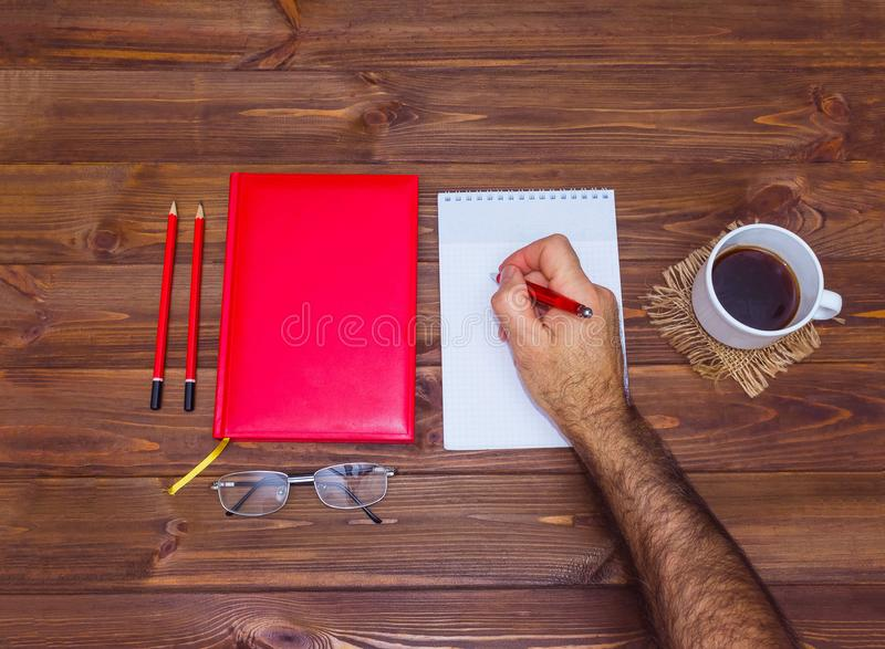 Note book and pencil with cup coffee on wooden table stock image