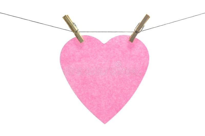 Note collante de coeur rose plat accrochée images stock