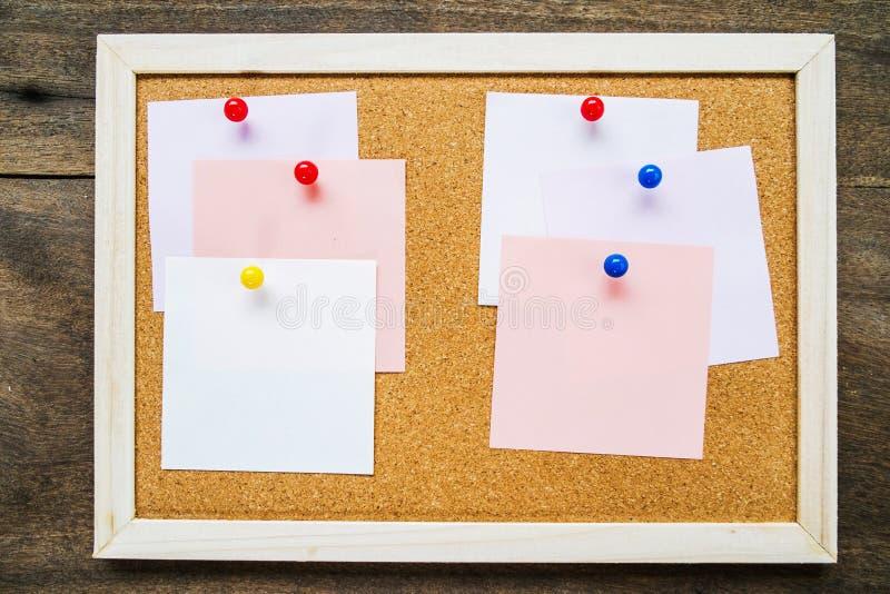 Note collante sur le panneau de liège sur le fond en bois de mur, l'espace vide images stock
