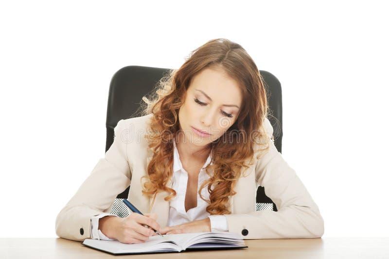 Note d'écriture de femme d'affaires par un bureau photographie stock