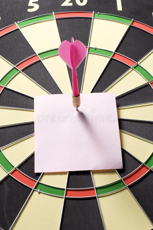 Note And Dart. Blank paper and dart board. You can put your writing here stock photo