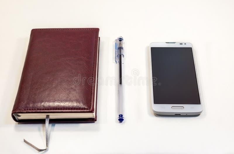 Note de Brown avec le stylo et téléphone sur la table images stock