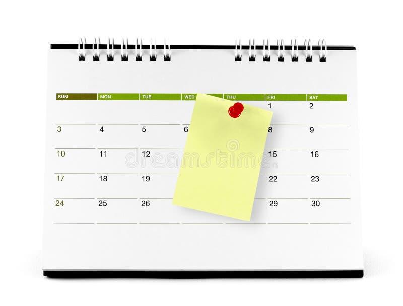 Note de papier jaune avec la punaise rouge à la page de calendrier photos stock