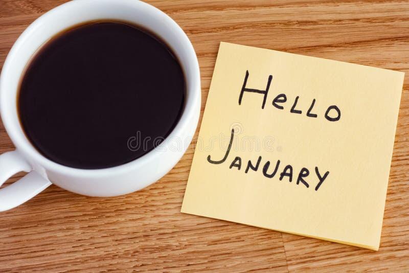 Note de post-it avec écrire le bonjour janvier et la tasse de café images libres de droits