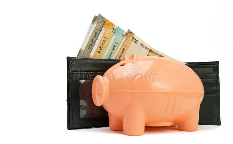 Note della rupia indiana in un portafoglio di cuoio nero sul porcellino salvadanaio dell'albicocca Successo e profitto e risparmi fotografie stock