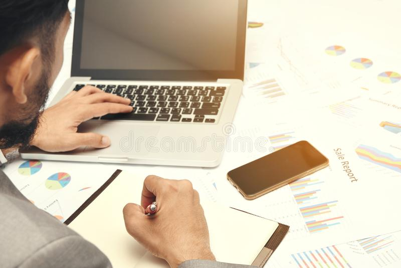 Note des textes d'écriture d'homme d'affaires et ordinateur se reposants d'utilisation sur le travail photographie stock libre de droits
