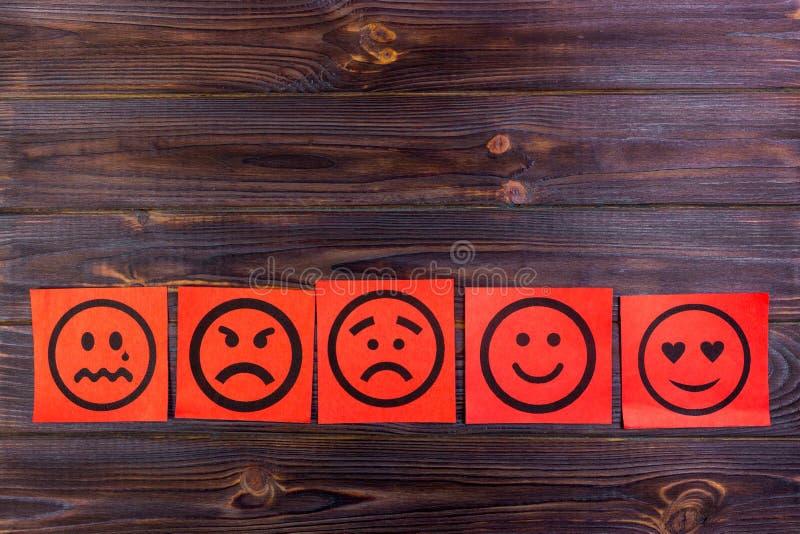 Note di carta rosse con felice, gioia, rabbia, la risata ed i fronti tristi sulla lavagna vignette immagini stock libere da diritti