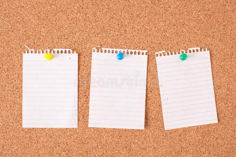 Note di carta sulla scheda del sughero fotografie stock
