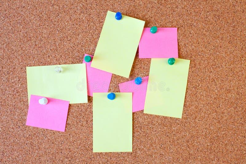 Note di carta sulla scheda del sughero immagine stock