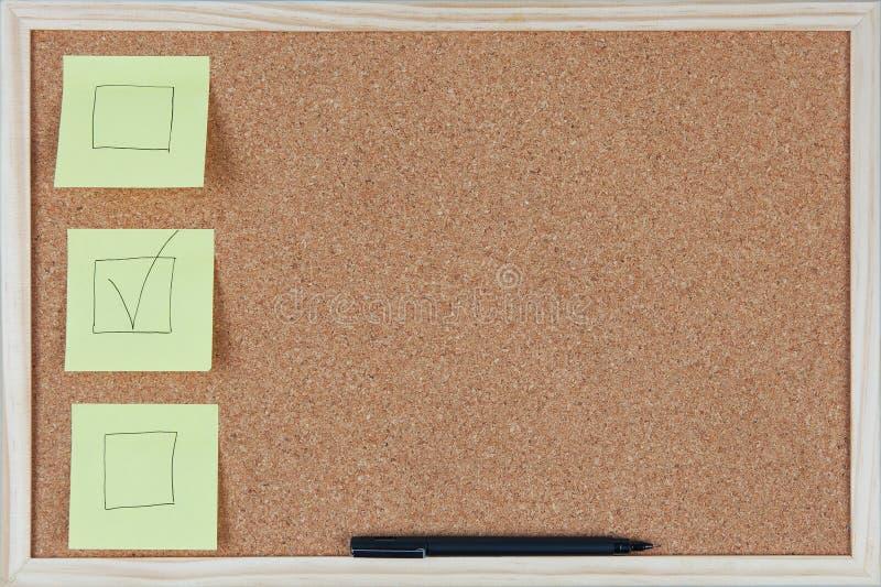 Note di Post-it di casella di controllo sul pannello di sughero immagine stock