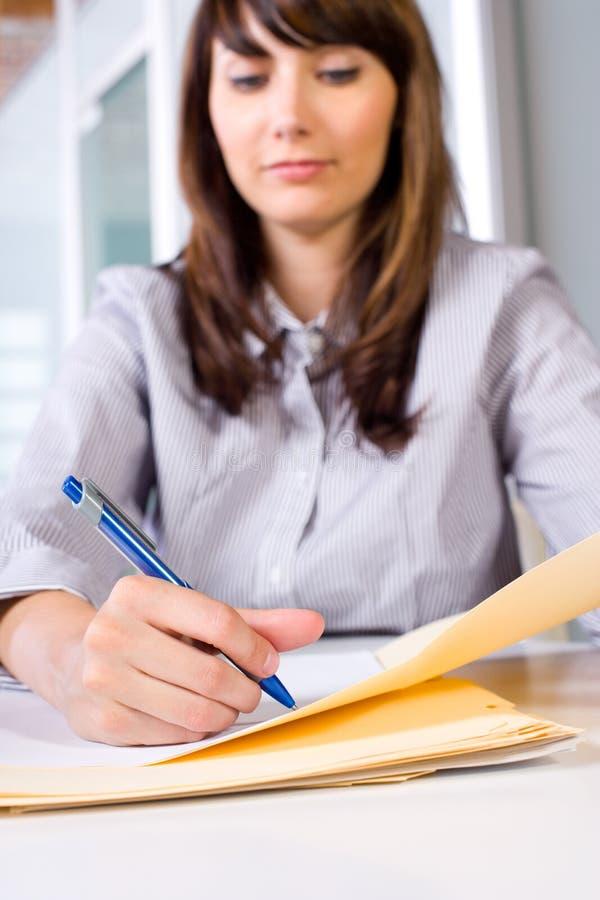 Note di scrittura della donna di affari allo scrittorio immagini stock libere da diritti
