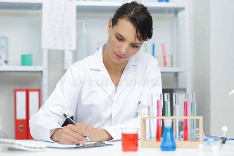 Note di scrittura della donna in laboratorio immagini stock