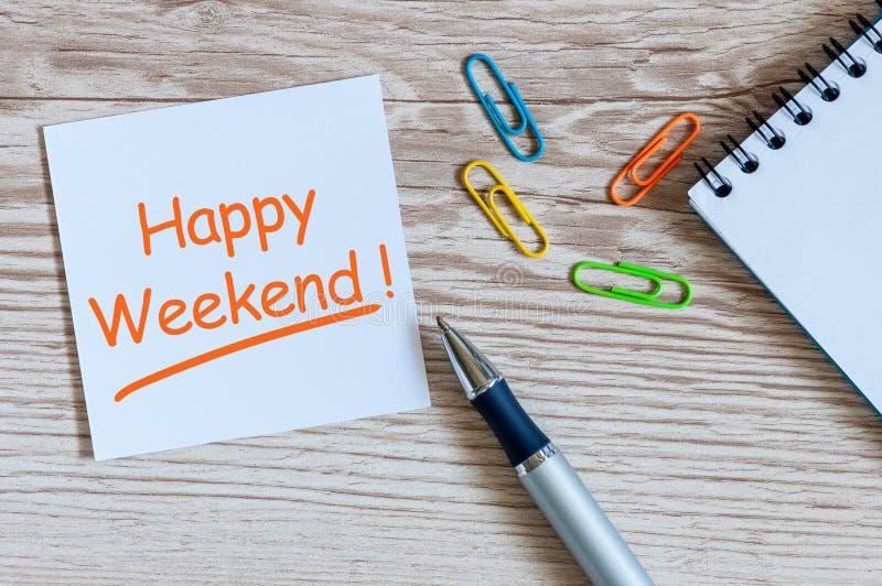 Note a escrita do fim de semana feliz na tabela com fontes, grampo do escritório, pena fotografia de stock