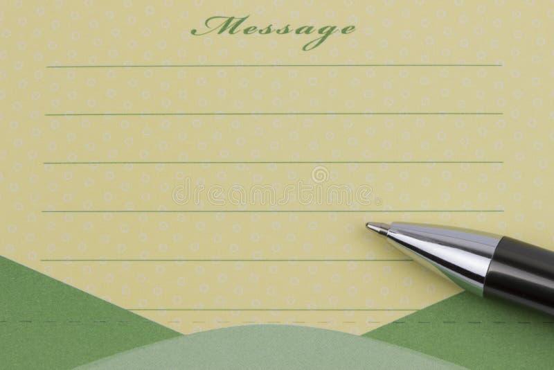 Note et stylo collants de message photographie stock