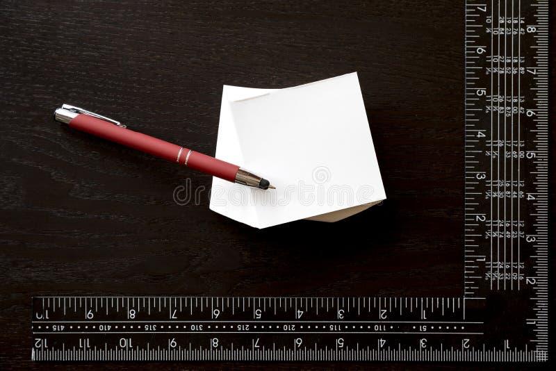 Note a etiqueta, a pena vermelha e o quadrado do ` s do carpinteiro foto de stock