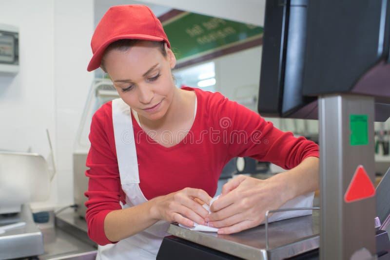 Note heureuse d'écriture de vendeuse au compteur dans la boucherie photos stock